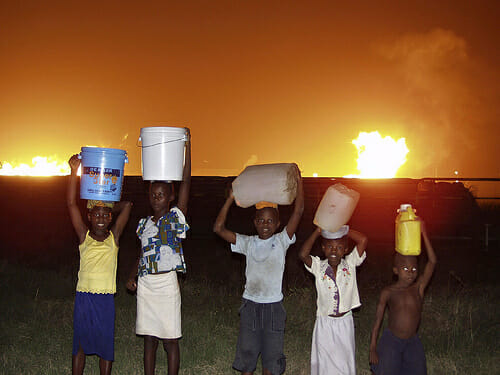 Children collect water from beside several gas flares at a flow station in the Niger Delta